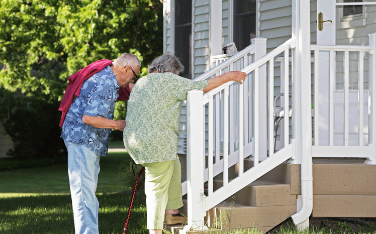 Elderly senior couple arriving home. He is helping her climb slowly up their back porch steps.